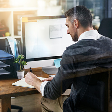Man working at desk in front of computer.